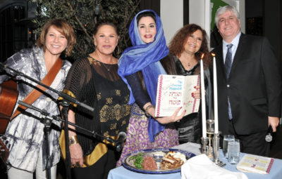 2015 Seder at Spago. As the candles are lit, Barbara Lazaroff stands with the Rabbi and Cantor as well as special guests Lanie Kazan and Melissa Manchester